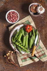 Concept of fresh green peas with ham over rusty background