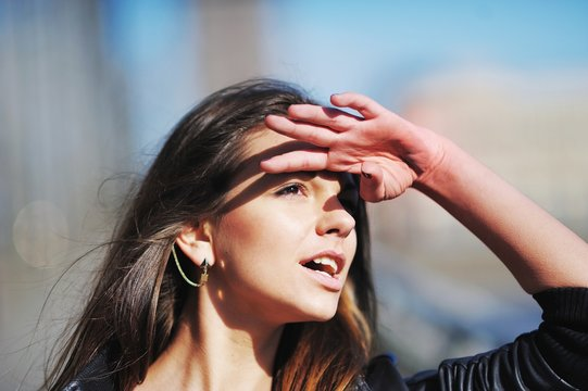 girl put her hand to his forehead to shield his eyes from the sun, looks up and wonders