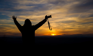 Silhouette of free and happy photographer with camera at sunset