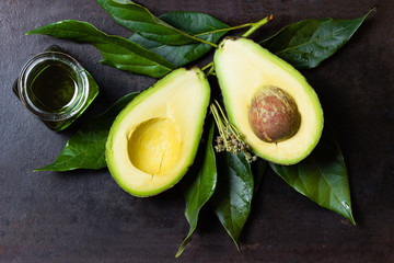Avocado with leaves and jar of oil on black background