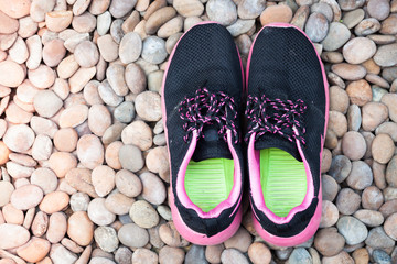 Running shoes in home garden on pebbles