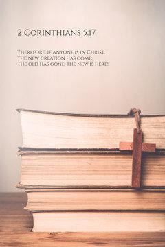 2 Corinthians 5:17 Vintage tone of wooden cross on book backgrou