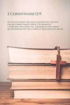 2 Corinthians 12:9 Vintage tone of wooden cross on book backgrou