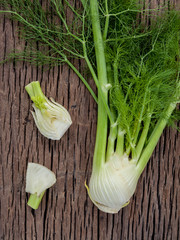 Fresh organic fennel bulbs for culinary purposes on wooden backg