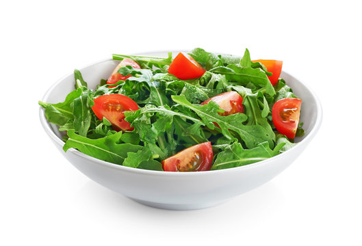 Bowl with fresh green salad arugula and tomatoes isolated on whi