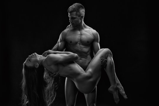 Nude sexy couple. Art photo of young adult man and woman. High contrast black and white muscular naked body