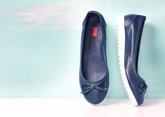 Slip on female blue flat shoes on wooden background.
