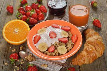 Muesli with yogurt, croissant and fresh strawberries