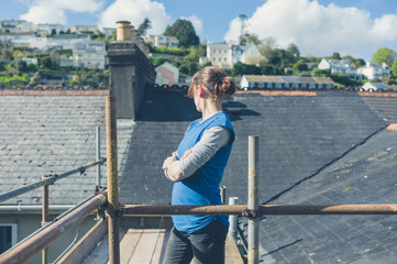 Young woman on scaffolding by roof