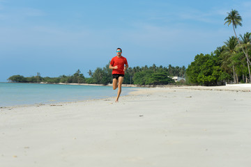 The man runs, runs on the beach, in the tropical country plays sports, with attached running a parachute behind the back