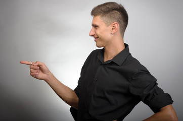 Young handsome businessman pointing to something using a finger. Left