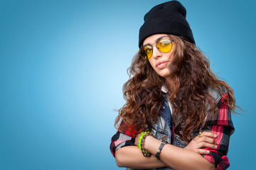 Cute hipster girl with long curly hair wearing red checkered shirt, denim vest, yellow glasses and black beanie hat posing at camera with crossed arms.