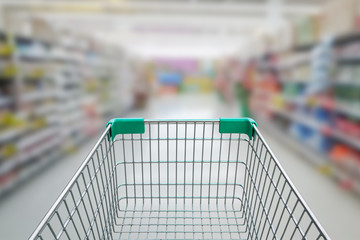 rear view of empty shopping cart with shopping mall or grocery b