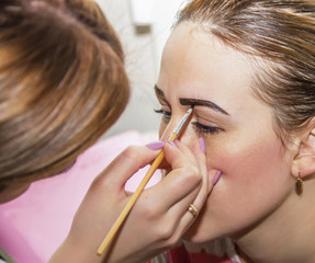 correction of eyebrows and modeling in a beauty salon, close-up,