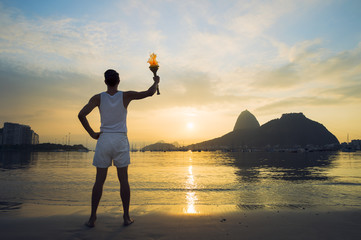 Athlete standing with sport torch against a scenic sunrise view of Sugarloaf Mountain and Botafogo Bay in Rio de Janeiro, Brazil