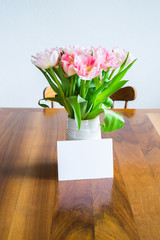 Tulips in blue vase and blank card on wooden dining table. Selective focus.
