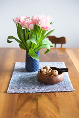 Tulips in blue vase and nuts in wooden bowl on wooden dining table. Selective focus on the nuts.