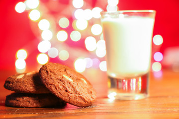 Cookies with milk on wooden table with christmas bokeh background