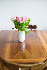 Tulips in blue vase on wooden table. Selective focus.