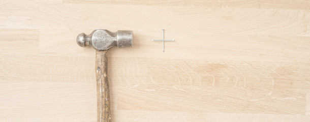 Old retro hammer and nails on wooden workbench