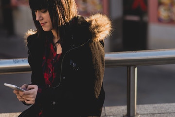 Young brunette woman using the phone on the street