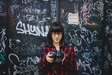Young woman using a camera on the street