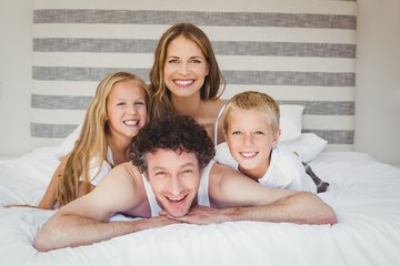 Portrait of family resting on bed