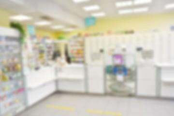 Pharmacy store drugs shelves interior blurred background