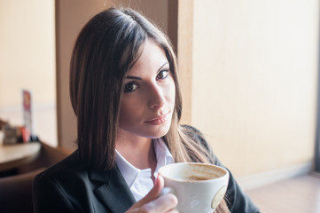 girl with unusual eyes in suit holding Cup of coffee
