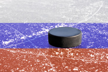 Black hockey puck on ice rink with Russian flag.