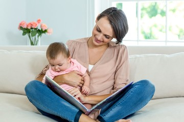 Mother showing picture book to son on sofa