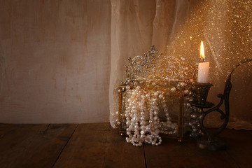 diamond queen crown, white pearls next to burning candle
