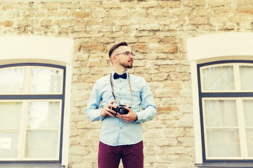 young hipster man with film camera in city