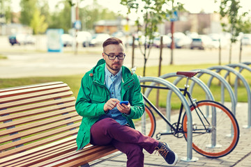 happy young hipster man with smartphone and bike