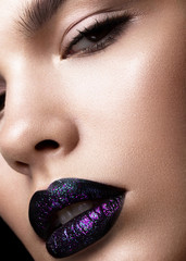 Portrait of a beautiful girl. Brilliant glossy lips closeup. Purple glitter on black lipstick