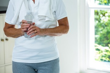 Mid section of senior woman standing with water bottle