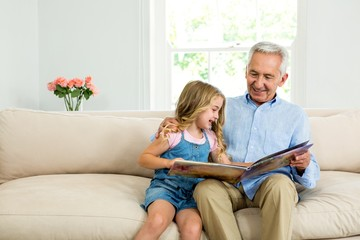 Smiling girl and granddad with picture book