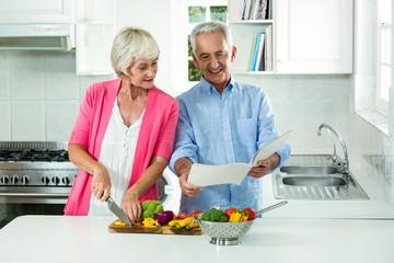 Happy senior couple with recipe book