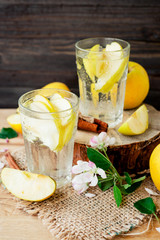 detox , healthy and refreshing drink ,Nutritious cold sparkling water with fresh apple and cinnamon on a wooden background