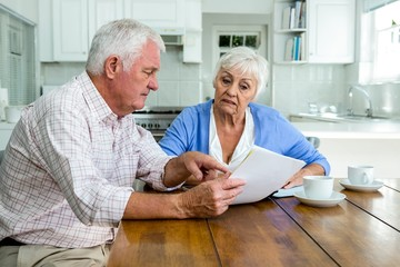 Retired couple discussing with documents