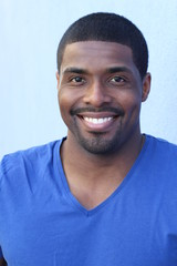 Vertical close up portrait of a happy black man in his 20s with a perfect smile isolated on a blue background