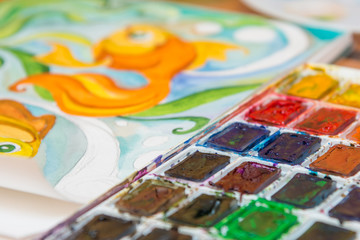 Close-up of watercolors and a fragment of the picture goldfish
