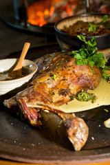 Delicious free range roasted goat shoulder served on a rustic metal plate by a hot open coal fire. Served with fresh parsley.