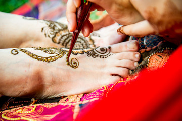 Picture of human legs being decorated with henna tattoo, mehendi