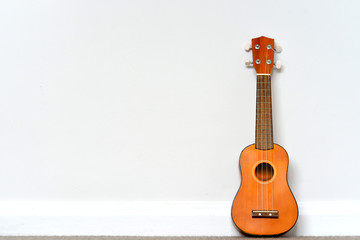 small orange Ukelele leaning on white wall