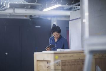 Young female engineer using digital tablet in an industrial plant, Freiburg im Breisgau, Baden-Württemberg, Germany