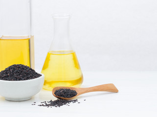 Sesame in a bowl and spoon  with oil in laboratory glass setup o