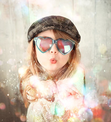 Child Blowing Colorful Sparkle Glitters
