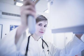 Young female doctor using x-ray machine in hospital, Freiburg im Breisgau, Baden-Württemberg, Germany