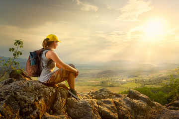 Portrait of woman with backpacker sitting on top of the mountain enjoying valley view Wall mural